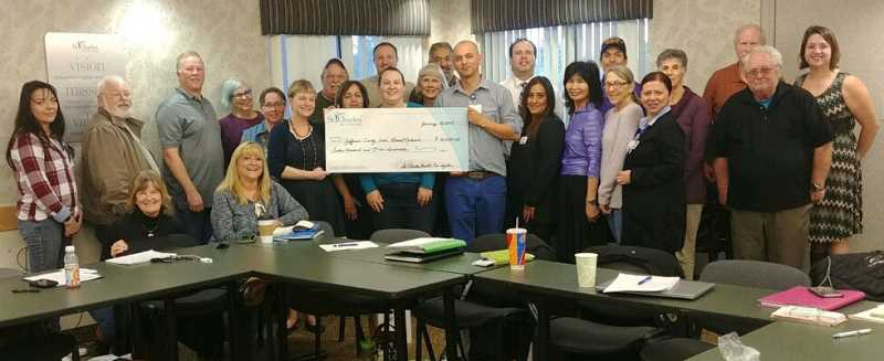 SUBMITTED PHOTO - Holding a giant grant check are LINC Director Austin Cooper, left, and check presenter Carlos Salcedo, manager of community partnerships for St. Charles Health System, right, with members of the Faith Based Network surrounding them.
