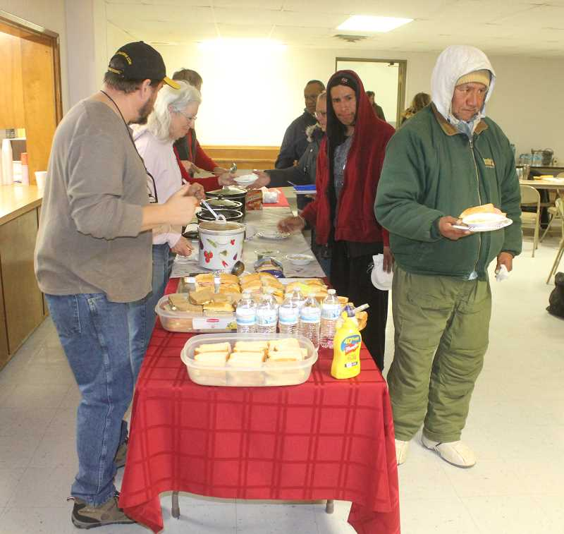 SUSAN MATHENY/MADRAS PIONEER - Volunteers serve a hot meal to homeless people at the Point in Time County.