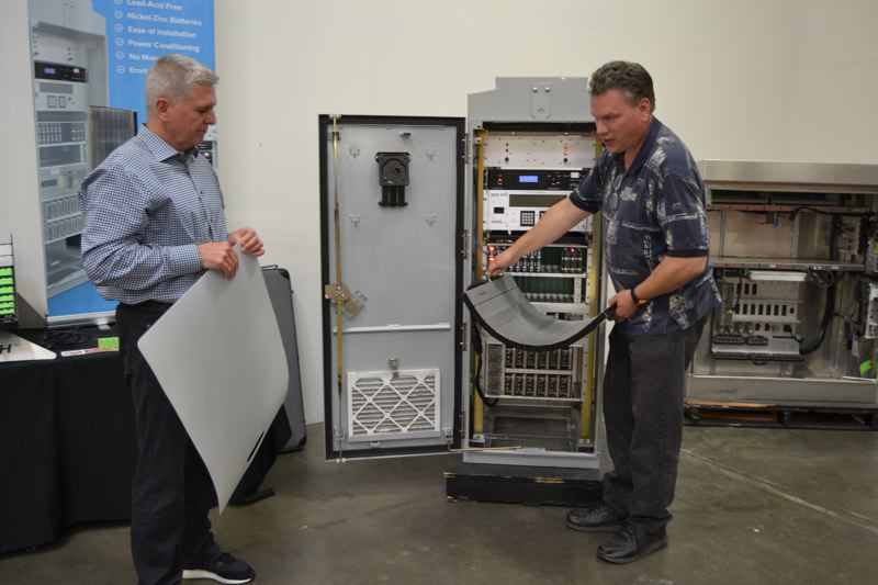 PAMPLIN MEDIA GROUP: FILE PHOTO - Vice President of research and innovation Dan Sisson (right) and CEO Tim Hysell install their bendy batteries in seconds, without deconstructing any part of the traffic cabinet.