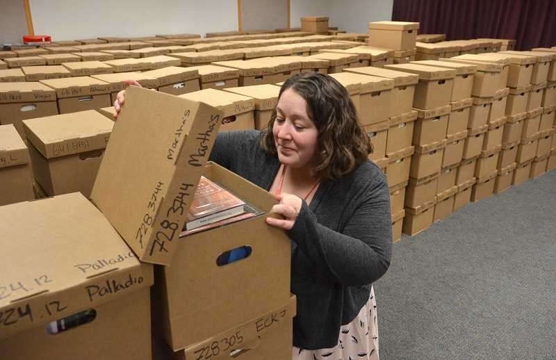 SPOKESMAN PHOTOS: VERN UYETAKE - Operations Manager Shasta Barnes amid boxes of book that have been packed for the childrens section of the library.