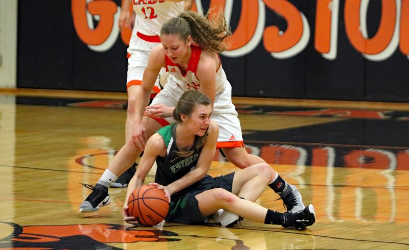 REVIEW/NEWS PHOTO: JIM BESEDA - Estacada's Karlye Nakashimada looks to make a pass while seated on the floor and under pressure from Gladstone's Aaliyah Asad in the first half of Tuesday's game at Gladstone.
