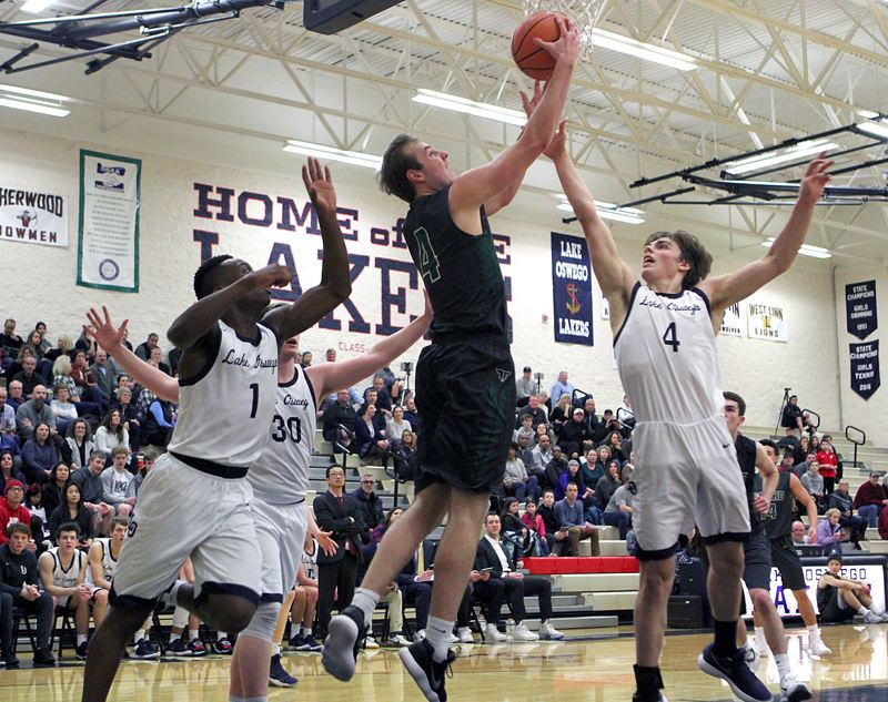PAMPLIN MEDIA GROUP PHOTO: MILES VANCE - Tigard junior wing Stevie Schlabach goes up for a reverse layin during the Tigers 64-42 loss at Lake Oswego High School on Friday.
