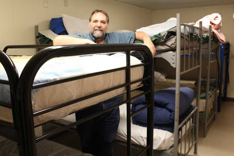 JASON CHANEY/CENTRAL OREGONIAN  - Redemption House Ministries Executive Director Greg Sanders stands amidst the bunk beds inside of Regeneration House, the local emergency men's shelter. The shelter reopened at a new location on the Madras Highway and began serving homeless men in early January.