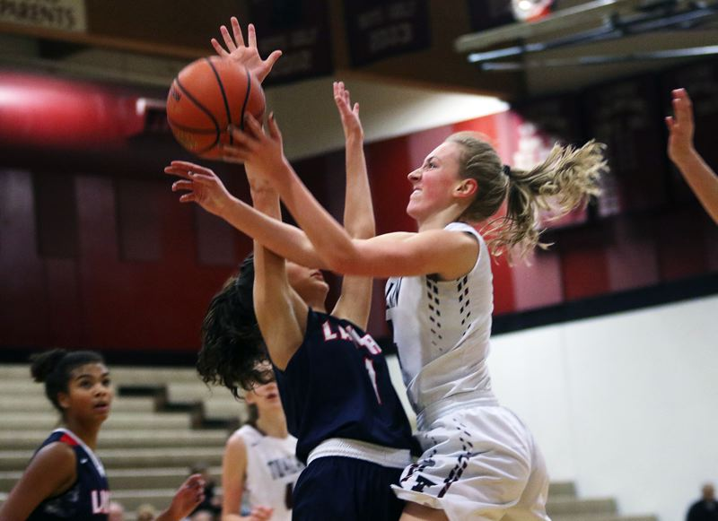 DAN BROOD - Tualatin High School junior Natali Denning (right) goes to the basket against Lake Oswego's Taylor Anders during Friday's Three Rivers League contest.