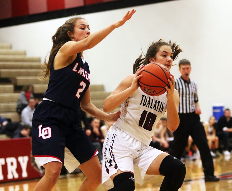DAN BROOD - Tualatin freshman Kasidy Javernick (right) keeps the ball away from Lake Oswego's Emma Jeanson during Friday's game.