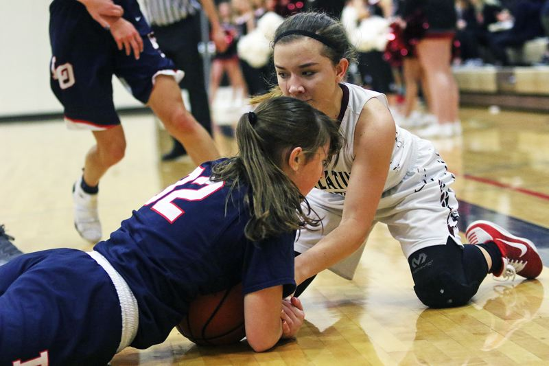 DAN BROOD - Tualatin senior Mikah Springer (right) battles Lake Oswego's Janie Ruttert for the ball.