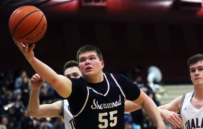 DAN BROOD - Sherwood senior post Jace Sucher reaches for the ball during Friday's game at Tualatin.