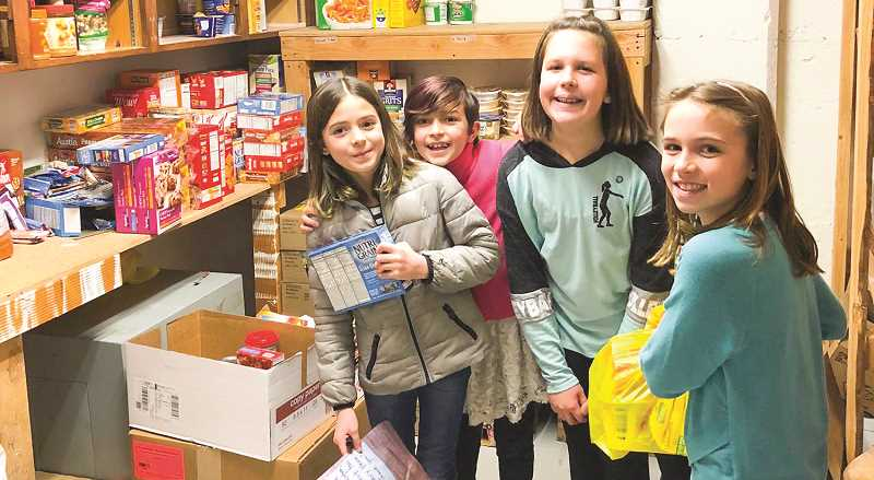 PHOTO COURTESY OF CROOK COUNTY ON THE MOVE - Elementary school students help stock the food pantry at Barnes Butte Elementary. Pictured above left to right are Mason Gattey, Abigail Gattey, Sawyer McDonald and Samantha Ramos.