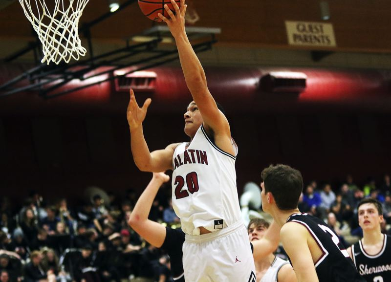 DAN BROOD - Tualatin sophomore John Miller goes up to the basket during the game with Sherwood.