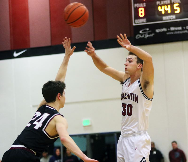 DAN BROOD - Tualatin senior Chris Freese (right) throws a pass over Sherwood senior Jordan Gregory.