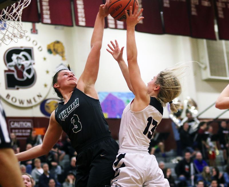 DAN BROOD - Tigard High School junior Campbell Gray (left) goes up to try and block a shot by Sherwood senior Lauren Scarvie during last week's game. The Tigers scored a 34-22 victory.
