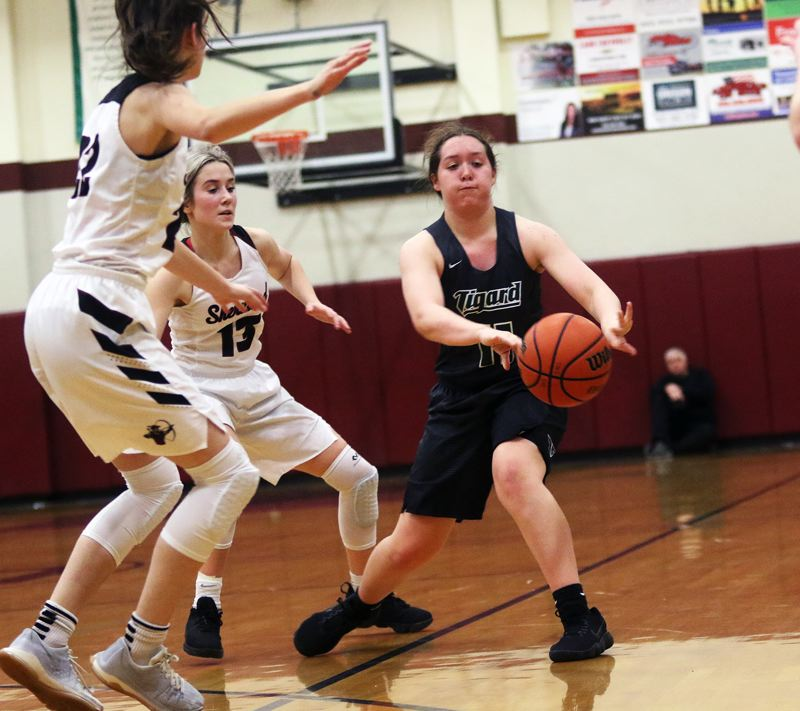 DAN BROOD - Tigard junior Paige LaFountain (right) throws a bounce pass during the game at Sherwood.