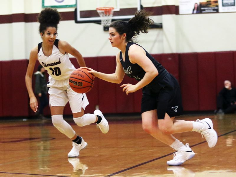 DAN BROOD - Tigard sophomore Kennedy Brown (right) looks to bring the ball up court in front of Sherwood freshman Kylah Williams.