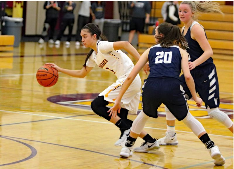 REVIEW/NEWS PHOTO: JIM BESEDA - Milwaukie's Ariana Sanchez finds an opening between Wilsonville defenders Emily Scanlan (20) and Reese Timm (5) during the second half of Wednesday's girls' basketball game at Milwaukie.