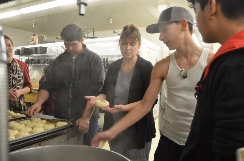 SPOTLIGHT PHOTO: NICOLE THILL - Janelle Gross, center, the owner of Scappoose Bagel, works with a group of students in the bakery math class at Scappoose High School on Monday, Jan. 22. After forming the bagels and letting them prove, she shows the students how to stretch them one more time before placing them in boiling water.