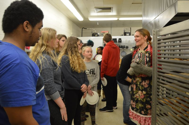 SPOTLIGHT PHOTO: NICOLE THILL - Scappoose High School math teacher Kellia Holzworth stands with a group of students waiting for finished bagels to come out of the oven. Students took on different roles in the bagel-making process, from shaping them, to boiling, to adding toppings, to baking.