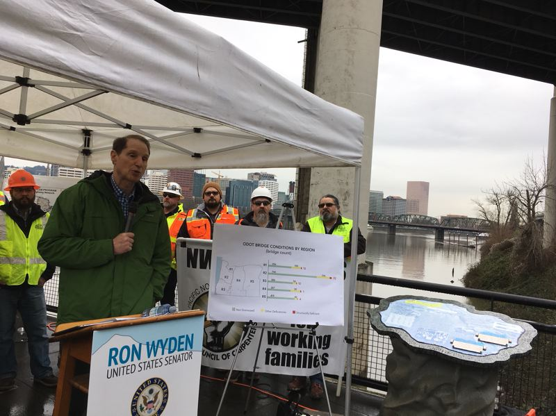 PAMPLIN MEDIA GROUP: PETER WONG - U.S. Sen. Ron Wyden, D-Ore., speaks on Thursday, Feb. 1, about the need for federal aid for road and bridge repairs near one of the pillars of the Marquam Bridge, which carries Interstate 5 across the Willamette River in Portland. In the background is the Hawthorne Bridge, which is maintained by Multnomah County.