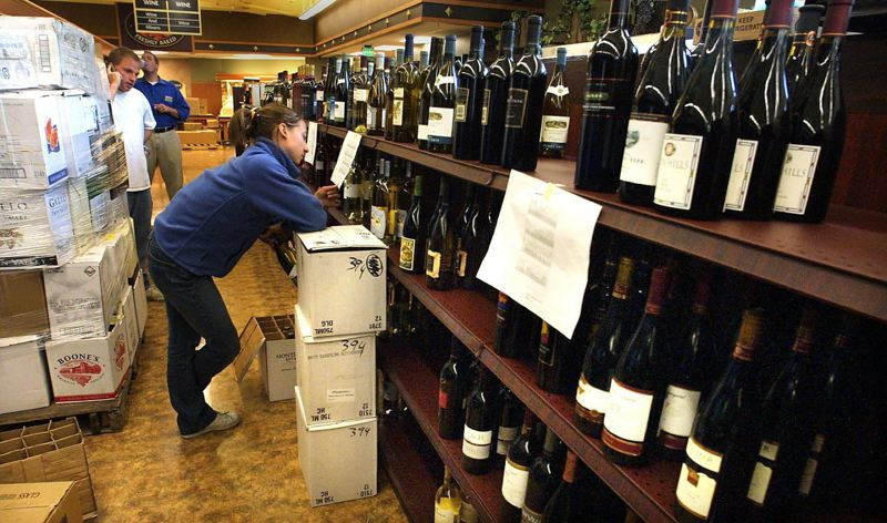 PAMPLIN MEDIA GROUP: FILE PHOTO - Megan Fabik of Columbia Distributing studies the display list before stocking the wine shelves at the new Safeway store along Southwest 10th Avenue.