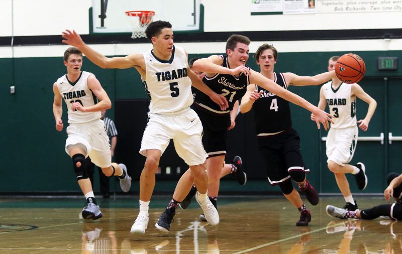 DAN BROOD - Tigard freshman Drew Carter (5) and Sherwood junoir Braden Thorn (21) try to chase down a loose ball during Friday's game. The Bowmen scored a 69-55 win.