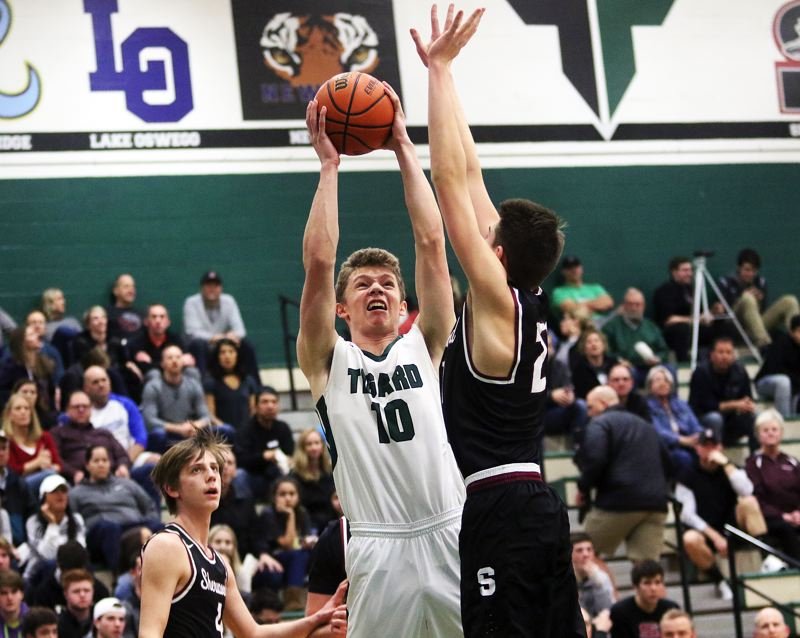DAN BROOD - Tigard senior post Austin Dufort (10) looks to shoot over Sherwood junior Braden Thorn.