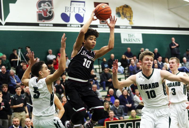 DAN BROOD - Sherwood sophomore guard Jamison Guerra goes up high as he looks to make a pass during Friday's game at Tigard.