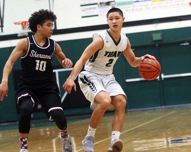 DAN BROOD - Tigard junior Jazz Ross (right) looks to get the ball up court against Sherwood sophomore Jamison Guerra.