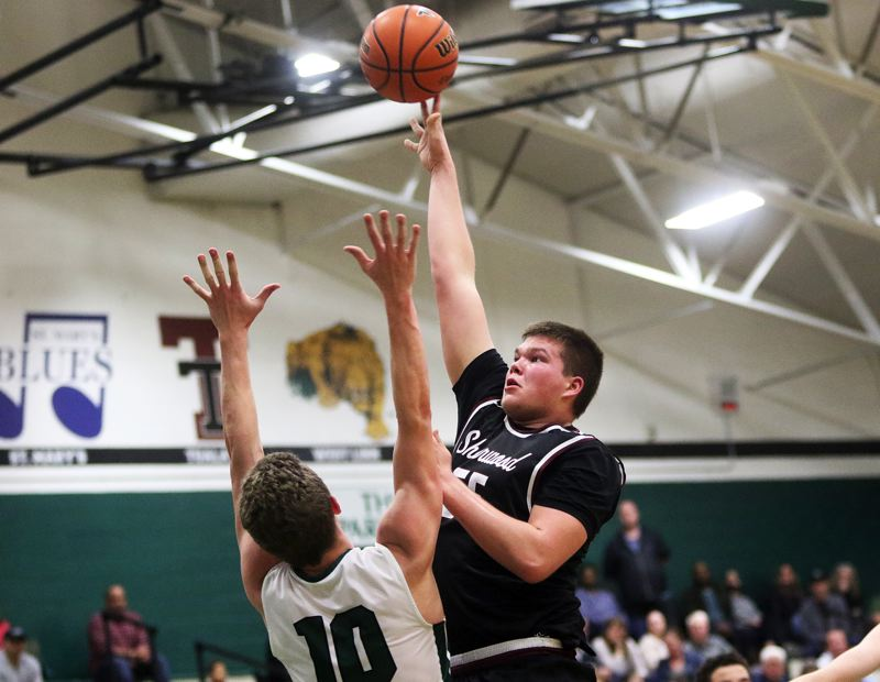 DAN BROOD - Sherwood senior Jace Sucher (right) puts up a shot over Tigard senior Austin Dufort during Friday's game.