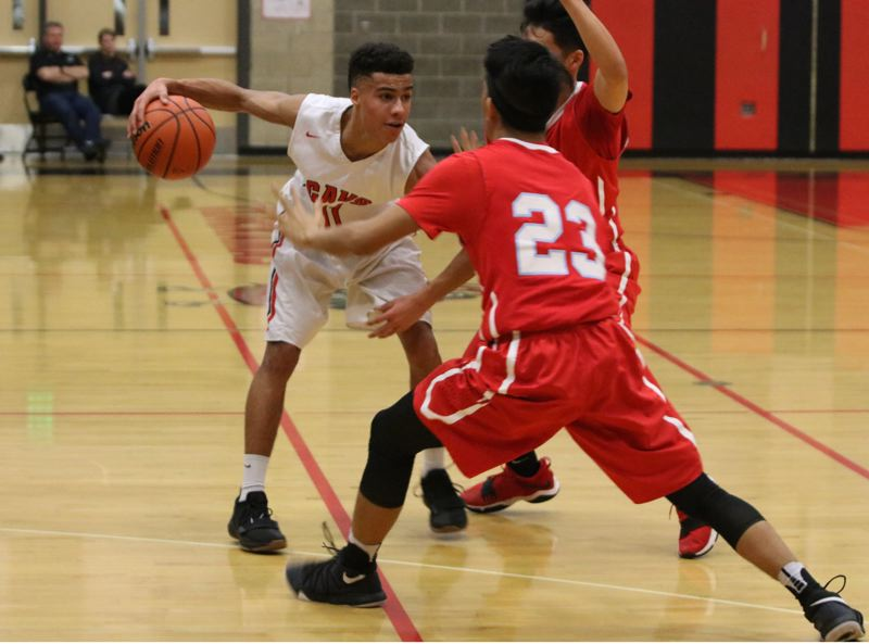 REVIEW/NEWS PHOTO: JIM BESEDA - Clackamas' Russell Gray runs into double-team pressure from Centennial's Sonam Phuntsok (partially hidden) and Jason Deleon (23) during the first half of Friday's game at Clackamas.