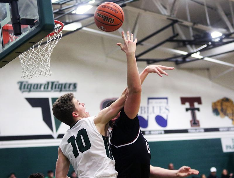 TIMES PHOTO: DAN BROOD - Sherwood senior post Jace Sucher opens the third quarter by scoring from short range with his back to the basket and turning in a three-point play during his team's 69-55 Friday win at Tigard High School.