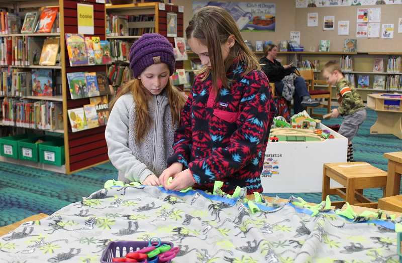 HOLLY SCHOLZ - Sisters Gabi, 8, and Sami, 10, Ramos help tie a no-sew fleece blanket during a Project Linus event at the Crook County Library last Thursday. Children helped make the blankets, which will be given to local children in need through the Family Access Network.