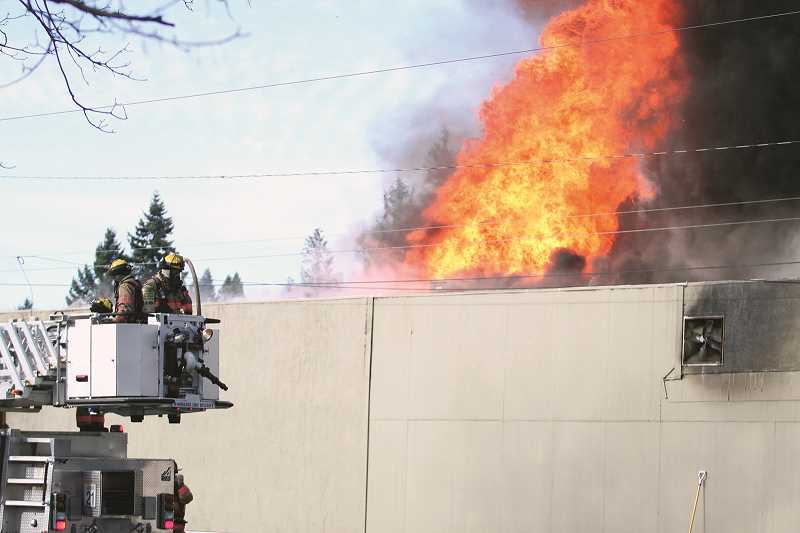 PHIL HAWKINS - Two ladder trucks from Woodburn and Silverton fire districts assisted firefighters in fighting the giant flames coming out of Young Street Market on Monday morning.