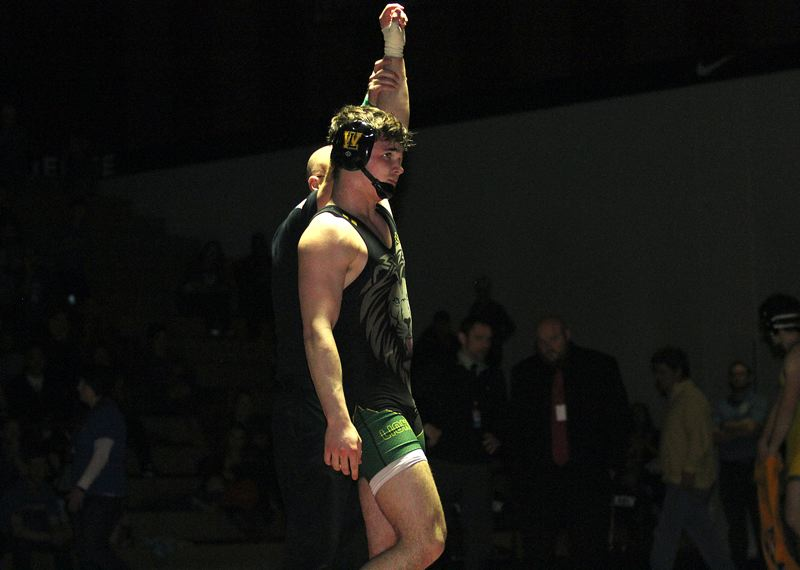 TIDINGS PHOTO: MILES VANCE - West Linn senior Brett Bell has his hand raised in victory after beating Tigard's Jacob Beck 12-6 in the 182-pound district final on Saturday at Tualatin High School.