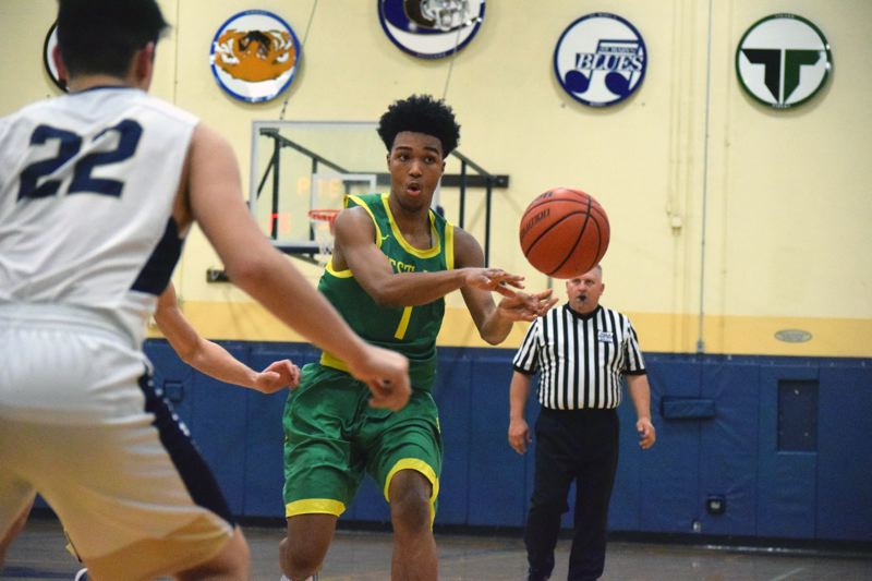 PAMPLIN MEDIA GROUP PHOTO: TANNER RUSS - West Linn sophomore guard Micah Garrett makes a pass during his team's 61-44 victory at Canby High School on Friday.