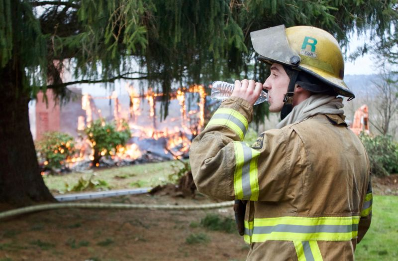 OUTLOOK PHOTO: CHRISTOPHER KEIZUR - A Sandy Firefighter takes a break during a live-fire training exercise at a home on Southwest Sturges Lane.