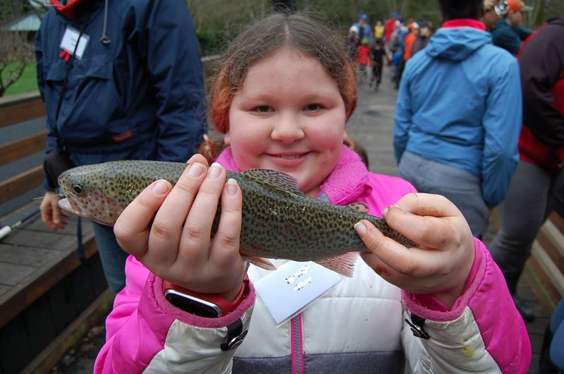 CONTRIBUTED PHOTO: ASSOCIATION OF NORTHWEST STEELHEADERS - A proud new angler shows off her fish at last years Northwest Steelheaders Family Fishing Camp. This years event will be held on the March 9-11 weekend.