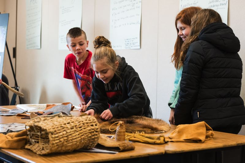 STAFF PHOTO: CHRISTOPHER OERTELL - Students in Lara McCabes fourth-grade class take a look at a sensory table full of artifacts from the Kalapuya Indians at Banks Elementary School.