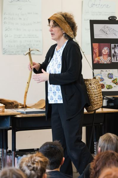 STAFF PHOTO: CHRISTOPHER OERTELL - Linda Hill, a Washington County Museum outreach educator, shows fourth-graders at Banks Elementary School how the Kalapuya Indians would carry a woven basket to harvest camas bulbs.