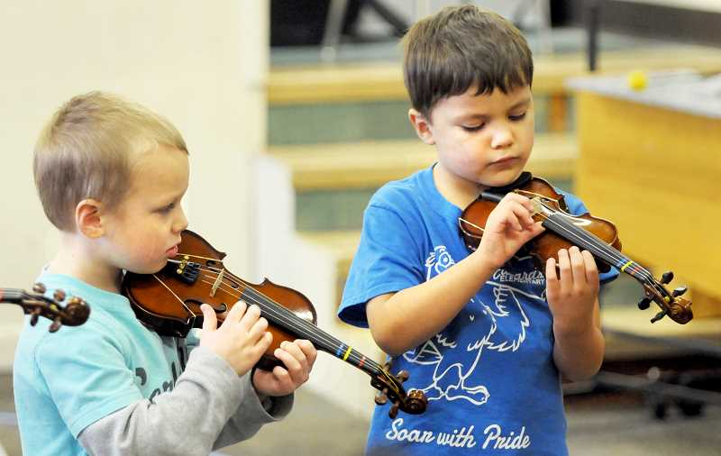 SETH GORDON - A pair of Edwards Elementary School kindergarten students pluck their violins during their first lesson using genuine violins Jan. 26. The school is participating in pilot program that will provide the instruments and instruction from kindergarten through second grade.