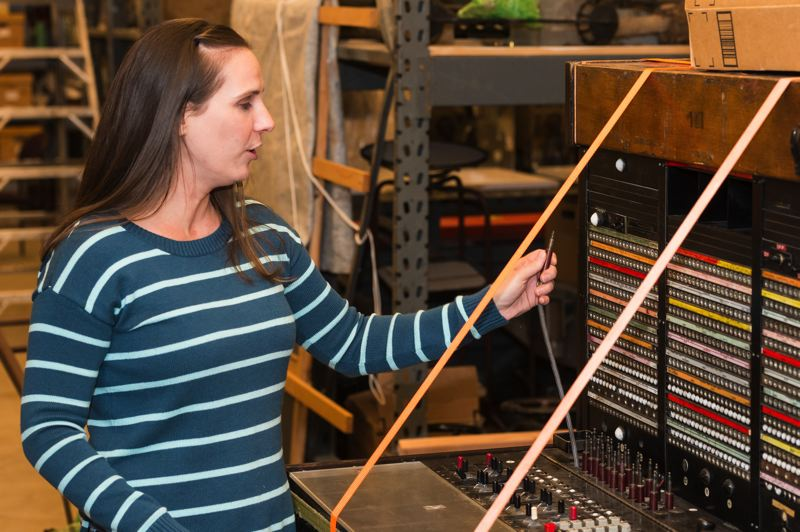 STAFF PHOTO: CHRISTOPHER OERTELL - Washington County Museum curator Liza Schade works an antique switchboard at the museum's PCC Rock Creek campus. The museum moved back to the site in October after five years in Hillsboro.