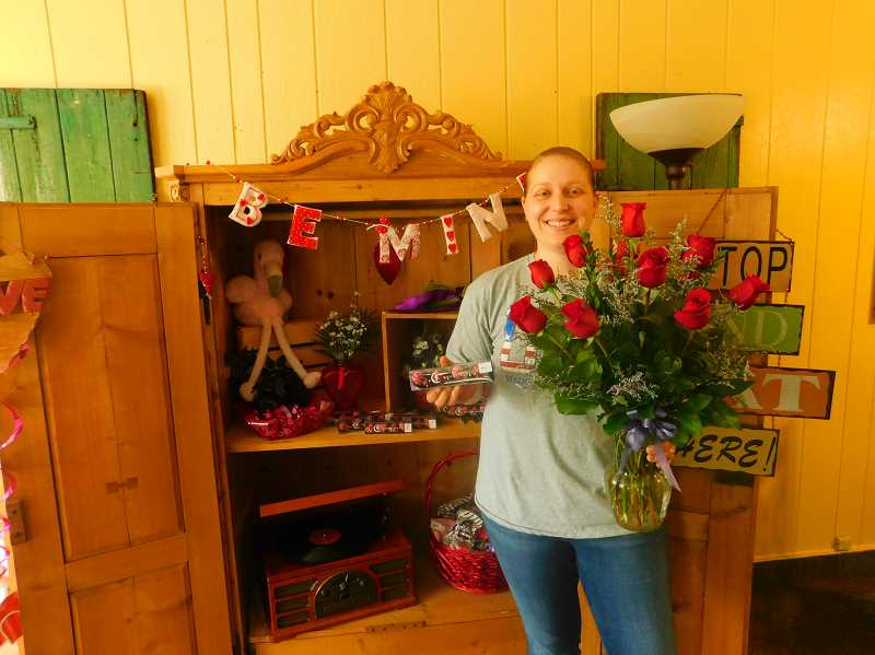 ESTACADA NEWS PHOTO: EMILY LINDSTRAND - Sara Lake of the Bloom Flower Shop shows off a Valentines Day floral arrangement. Lake said the holiday is one of the busiest times of the year at the shop.