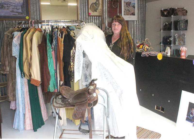 SUSAN MATHENY/MADRAS PIONEER - Juniper Auctions owner Cindy Fisher shows a 1950s wedding dress, which is part of her next vintage clothing auction. Customers can preview other items at the shop, such as the child's saddle in front.