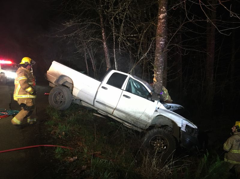 COURTESY PHOTO: FOREST GROVE FIRE & RESCUE - Forest Grove Fire & Rescue and other agencies respond to a single-vehicle crash that trapped a man inside this pickup truck for more than an hour on Dixon Mill Road Tuesday night, Feb. 6.