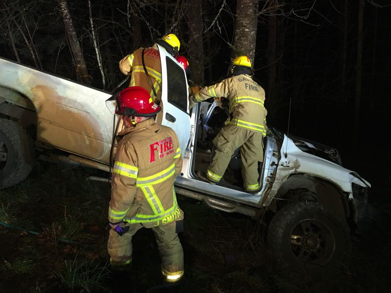 COURTESY PHOTO: FOREST GROVE FIRE & RESCUE - Firefighters from Forest Grove Fire & Rescue and the Gaston Fire District work on a pickup truck that smashed into a tree east of Gaston on Tuesday, Feb. 6, trapping its single occupant inside.