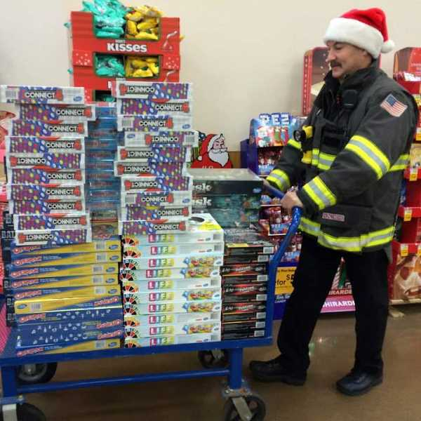 COURTESY PHOTO - Each December, Hillsboro Firefighter Random Acts delivers toys and meals to families in need.