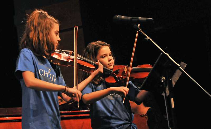 REVIEW PHOTO: VERN UYETAKE - Lake Oswego twins Sarah and Sophia Fisher were featured Saturday in the Honor Choir's performance of 'Mayim, Mayim.' The young violinists are students at Westridge Elementary School.