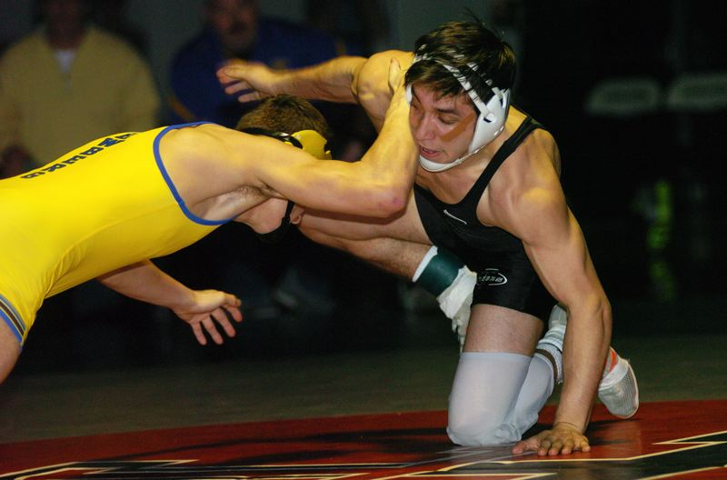 DAN BROOD - Tigard High School junior Emilio Jimenez (right) battles Newberg's Jack Evans in the 132-pound district tournament final on Saturday.
