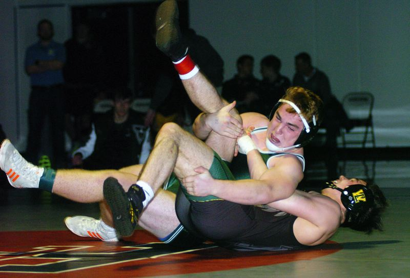 DAN BROOD - Tigard senior Jacob Beck (top) battles West Linn's Brett Bell in the 182-pound championship match at the Three Rivers Leauge district tournament.