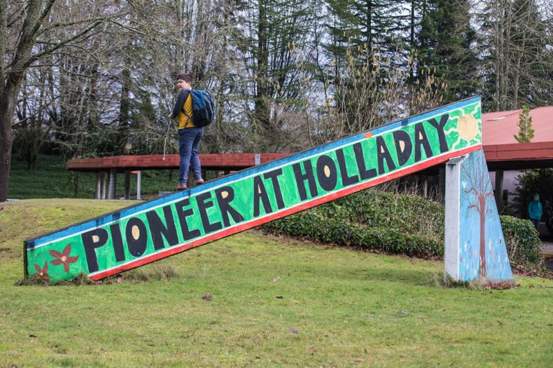 TRIBUNE PHOTO: JONATHAN HOUSE - Mack walks along the sign for Pioneer School in Southeast Portland. A planned move of the school has parents worried that the new destination will be worse than the Holladay campus.