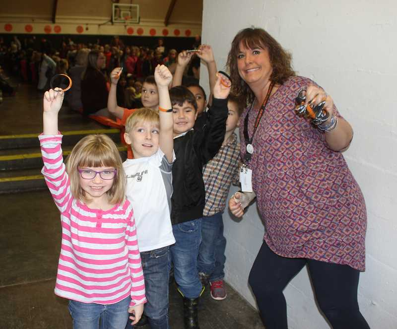 "SUSAN MATHENY/MADRAS PIONEER - Culver kindergarteners, from front left, Harper Keegan, Hayden Wallman, Liam Sando and classmates, hold up pledge bracelets given out by their teacher Jamie Fritz, at right. Students pledged to try to ""Lift Each Other Up"" over an 18-week period."