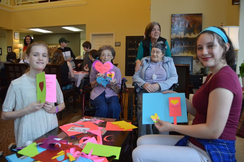 SPOTLIGHT PHOTO: NICOLE THILL - Ayla Power, Elsie Lacey, Millie Gobel and Anne Selby hold up some of the Valentine's Day cards they completed on Thursday, Feb. 8 at the Brookedale Rose Valley Senior Center in Scappoose.